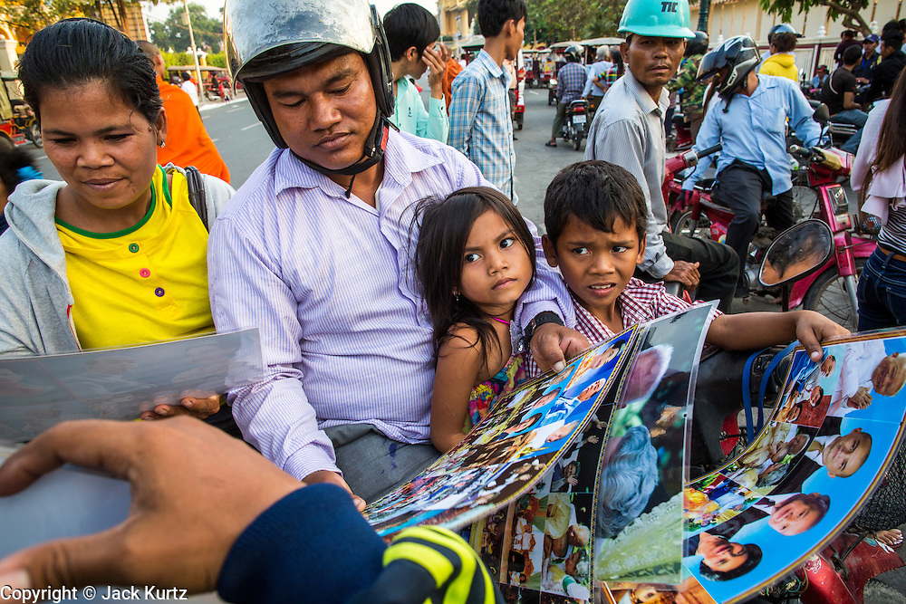 """30 JANUARY 2013 - PHNOM PENH, CAMBODIA: A family on a motorscooter looks at portraits of former Cambodian King Norodom Sihanouk in front of the National Museum in Phnom Penh. Sihanouk (31 October 1922- 15 October 2012) was the King of Cambodia from 1941 to 1955 and again from 1993 to 2004. He was the effective ruler of Cambodia from 1953 to 1970. After his second abdication in 2004, he was given the honorific of """"The King-Father of Cambodia."""" Sihanouk held so many positions since 1941 that the Guinness Book of World Records identifies him as the politician who has served the world's greatest variety of political offices. These included two terms as king, two as sovereign prince, one as president, two as prime minister, as well as numerous positions as leader of various governments-in-exile. He served as puppet head of state for the Khmer Rouge government in 1975-1976. Most of these positions were only honorific, including the last position as constitutional king of Cambodia. Sihanouk's actual period of effective rule over Cambodia was from 9 November 1953, when Cambodia gained its independence from France, until 18 March 1970, when General Lon Nol and the National Assembly deposed him. Upon his final abdication, the Cambodian throne council appointed Norodom Sihamoni, one of Sihanouk's sons, as the new king. Sihanouk died in Beijing, China, where he was receiving medical care, on Oct. 15, 2012. His cremation is scheduled to take place on Feb. 4, 2013. Over a million people are expected to attend the service.        PHOTO BY JACK KURTZ"""