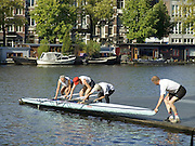 group of senior people letting a professional canoe into the water