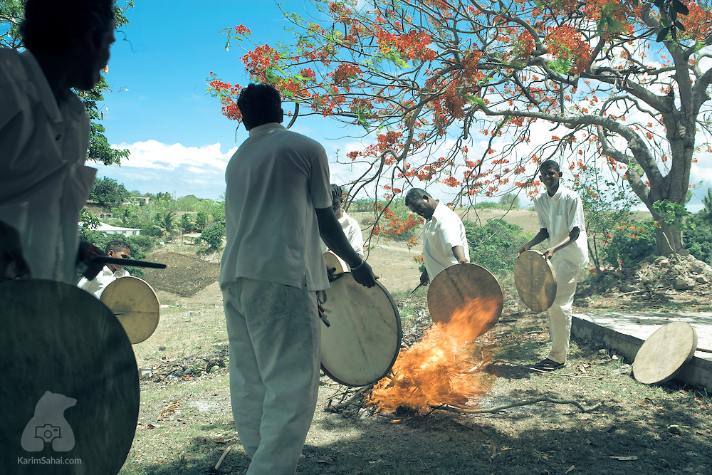 Musicians use the heat of a burning fire to tighten the skin on their percussion instruments, Le Moule, Guadeloupe.<br /> <br /> The instruments accompany a religious ritual whose origins can be traced back to South India.