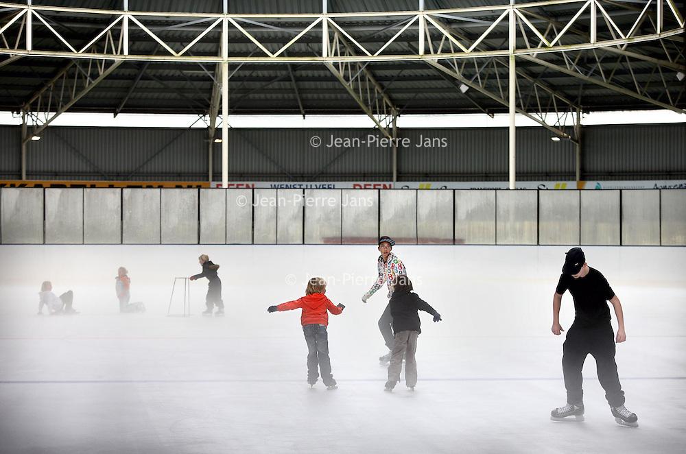 Nederland, Hoorn , 5 november 2010..Kinderen oefenen schaatsen op de binnenbaan  van Schaatsbaan de Westfries.Over de schaatsbaan hangt een mist van de kou..IJsbaan De Westfries voor vrijschaatsen, schaatslessen, een kinderfeestje, een sportief personeelsevenement, een winterse kerstborrel of een vergadering .In  the  winter the Dutch skate on rinks everywhere in the country. Children having a skating lesson.