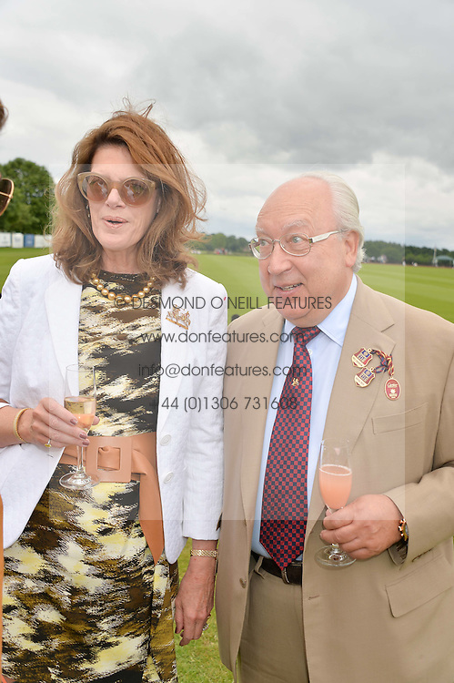 URS SCHWARZENBACH and his wife FRANCESCA at the Cartier Queen's Cup Final polo held at Guards Polo Club, Smith's Lawn, Windsor Great Park, Egham, Surrey on 15th June 2014.