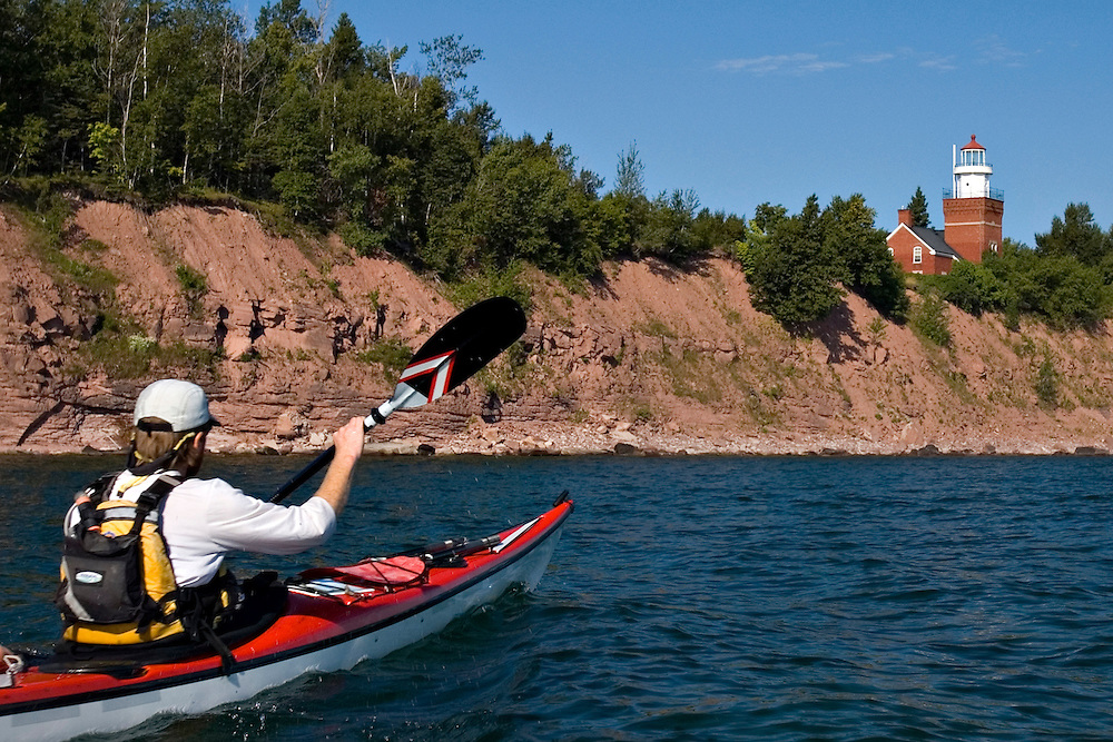 A sea kayaker approaches the Big Bay Point Lighthouse on Lake Superior in Big Bay Michigan.