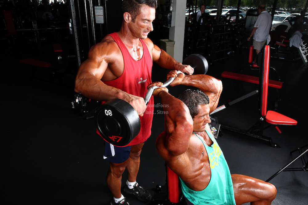 Bodybuilders Dan Decker and Brian Yersky doing seated ez-bar triceps workout.