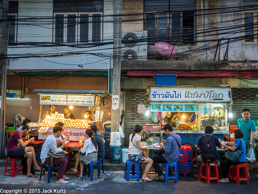 12 JUNE 2015 - BANGKOK, THAILAND:     People eat on the sidewalk on Sukhumvit Soi 38, one of the most famous street food areas in Bangkok. The food carts and small restaurants along the street have been popular with tourists and Thais alike for more than 40 years. The family that owns the land along the soi recently decided to sell to a condominium developer and not renew the restaurant owners' leases. More than 40 restaurants and food carts will have to close. The first wave of closings could start as soon June 21 and all of the restaurants are supposed to close over the next several months.      PHOTO BY JACK KURTZ