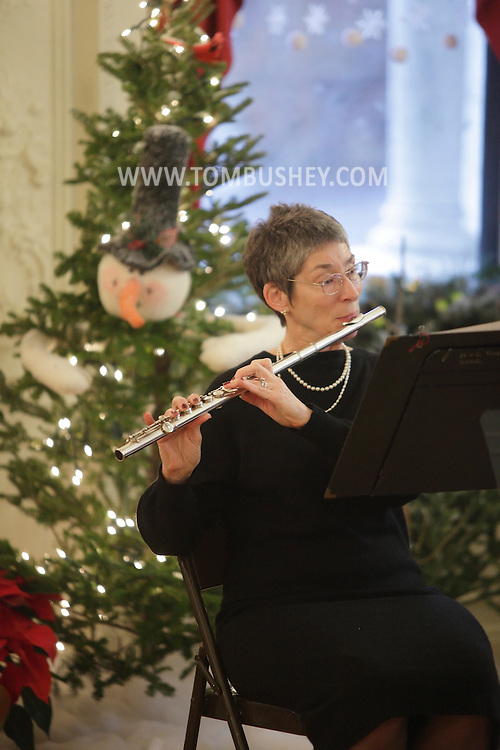 Middletown, New York - Patricia Eisenhart of the SUNY Orange Chamber Ensemble plays the flute during a concert at the Holiday Open House at the Morrison Hall mansion on Dec. 12, 2010. Morrison Hall was the home of the Morrison family, who donated the mansion to the college in 1950. The building is richly appointed with original Tiffany fixtures, lavish woodwork and C.W. Dodge ceiling murals.
