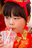 A young girl dressed in traditional kimono takes a break from parading through the streets on a large palanquin.