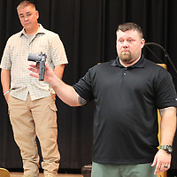 Billy Richey shows a plastic gun to illustrate how similar toys look to real guns. He and Tim Oswalt, left, led a safety seminar hosted by the Monroe County Chamber of Commerce last week.