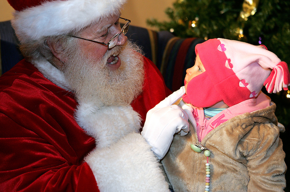 Santa (Jerry Swan), left, coaxes a smile from eight month old Isla Woodruff, seeing St. Nick for the first time. (By Jonathan Palmer, Special to The Courier-Journal) December 6, 2008