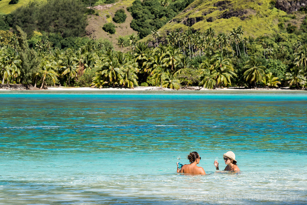 Two girls chat with a glass of white wine while bathing in the warm waters of the lagoon of Moorea.