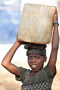 A boy carries a jerrican of water on his head in the Clara Town slum of Monrovia, Montserrado county, Liberia on Thursday April 5, 2012.