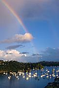 boats moored in Matauwhi Bay with rainbow