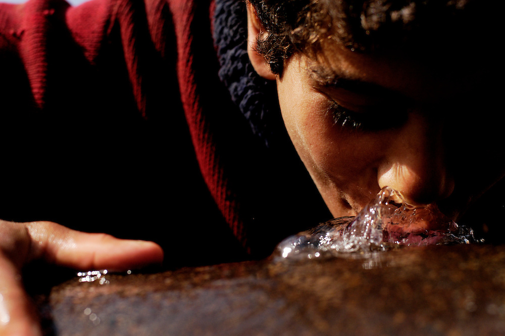 A young Iraqi boy drinks water leaking from a water main in the al-Maamil neighborhood, located on the outskirts of Baghdad.