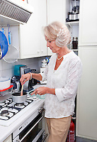 Senior woman cooking at kitchen counter