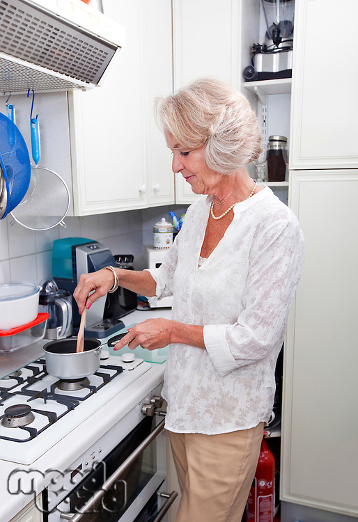 Senior woman cooking at kitchen counter