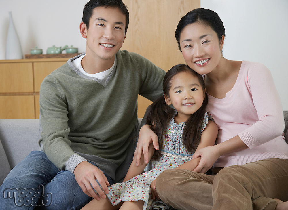Young couple and daughter Posing on Sofa