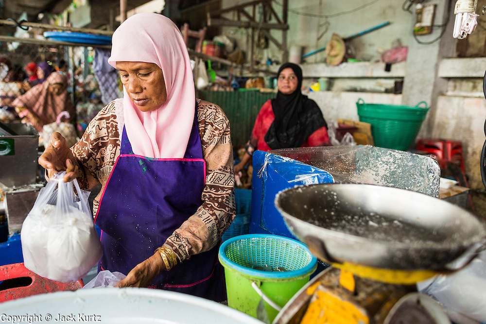 09 JULY 2013 - PATTANI, PATTANI, THAILAND: A Muslim woman sells coconut milk in the market in Pattani.  Pattani, along with Narathiwat and Yala, are the only three Muslim majority provinces in Thailand.     PHOTO BY JACK KURTZ
