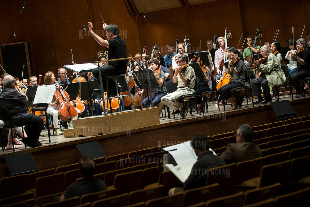 June 3, 2014 - New York, NY : As part of the New York Philharmonic Biennial, the orchestra solicited pieces from little-known composers and will choose three to play. Pictured here, Philharmonic Music Director Alan Gilbert, on podium, leads the New York Philharmonic as it performs a composition by composer Max Grafe, who is visible at foreground center, working with mentor composer Robert Beaser, far right, on Tuesday. CREDIT: Karsten Moran for The New York Times