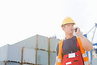 Male worker using walkie-talkie in shipping yard