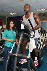 Access to services, Fitness instructor with disabled man in the gym; using body building sports equipment,