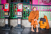 17 APRIL 2013 - BANGKOK, THAILAND:   A Buddhist monk waits to board a train back to his province after Songkran in Hua Lamphong Train Station in Bangkok. Songkran, the traditional Thai New Year, is the busiest time of the year for Thai domestic travel. Many people in Bangkok return to their home provinces for the holiday and some people in the provinces travel to Bangkok for the holiday. Songkran, usually a three day holiday, was five days this year because the official days on the weekend. Trains and buses coming into Bangkok were reported to be fully booked and the State Railway of Thailand added extra trains and carriages to accommodate the crowds.  PHOTO BY JACK KURTZ