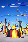 Colorful tents and kites on the beach at a coastal kite festival.