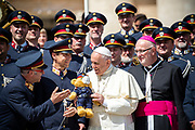 Pope Francis reacts as he receives a teddy baby bear as a present from musical band of the Austrian police, at the end of his weekly general audience in St Peter's square at the Vatican on April 25, 2018.