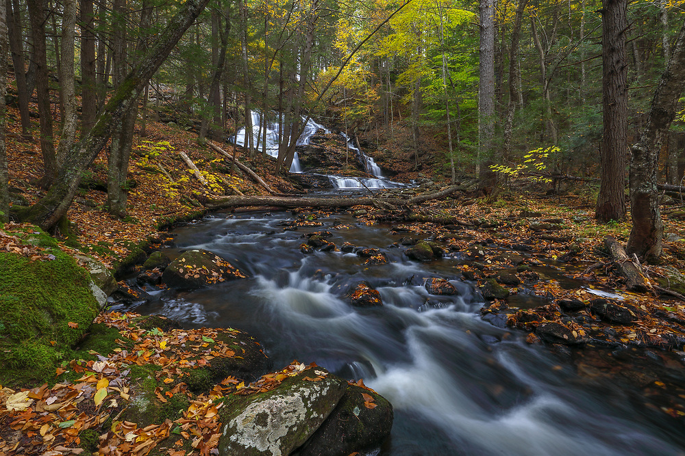 This fall I returned to Southern New Hampshire for another exquisite waterfall photography adventure. Old Wilton Falls must be one of the most beautiful waterfalls in New Hampshire and probably one of the most scenic waterfalls in all of New England. After a rainy fall day waterflow was good and I arrived early enough to make good use of the morning light. Equipped with a variety of Lee filters I create a silky water effects through a long exposure of multiple seconds and was able to control the light between darker foregrounds and brighter parts of the scenery. This image shows a different perspective of Garwin Falls further downstream and focuses on the brook and forest environment.    <br />