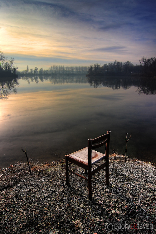 I took this picture on a very cold morning of January, from the bank of the Po River near to Carignano in Piedmont, Italy. I was wandering along the bank looking for something interesting to be included in the foreground, and I was immediately attracted by the frost on that chair. I realized that the chair, the frost, together with the two pole supports worked perfectly as a totally unexpected, somewhat striking foreground for the peaceful scene around. And all the elements together were telling the story of a fisherman that didn't go to fish that morning, as it was too cold..I set the camera and tripod on place and then just waited for the sky to break up. I was particularly lucky to have some direct sunlight hitting for a few moments the chair, thus producing that beautiful glow on the frost.