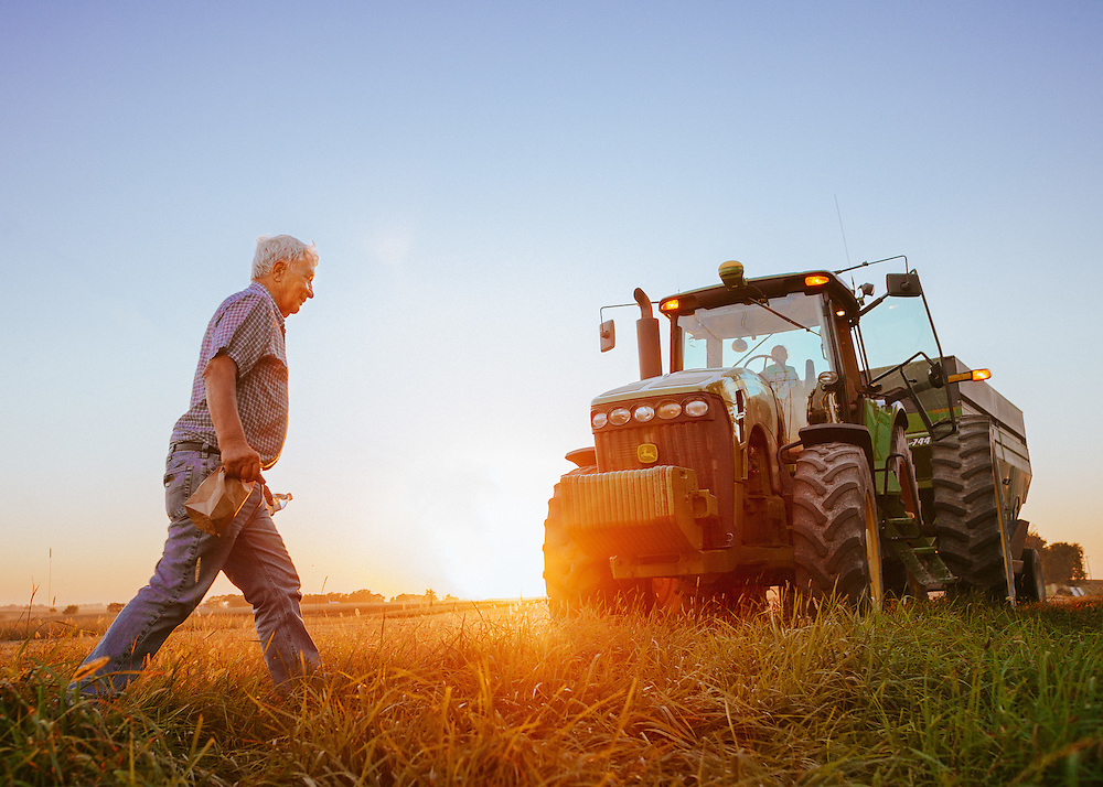 Farmers and a tractor on a farm in Iowa.<br /> Photographed by editorial lifestyle Texas photographer Nathan Lindstrom.