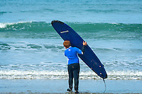 Boy carrying surfboard into sea<br /> Whitesands Bay<br /> Near St David's<br /> Surfing<br /> Pembrokeshire<br /> South<br /> Activities and Sports