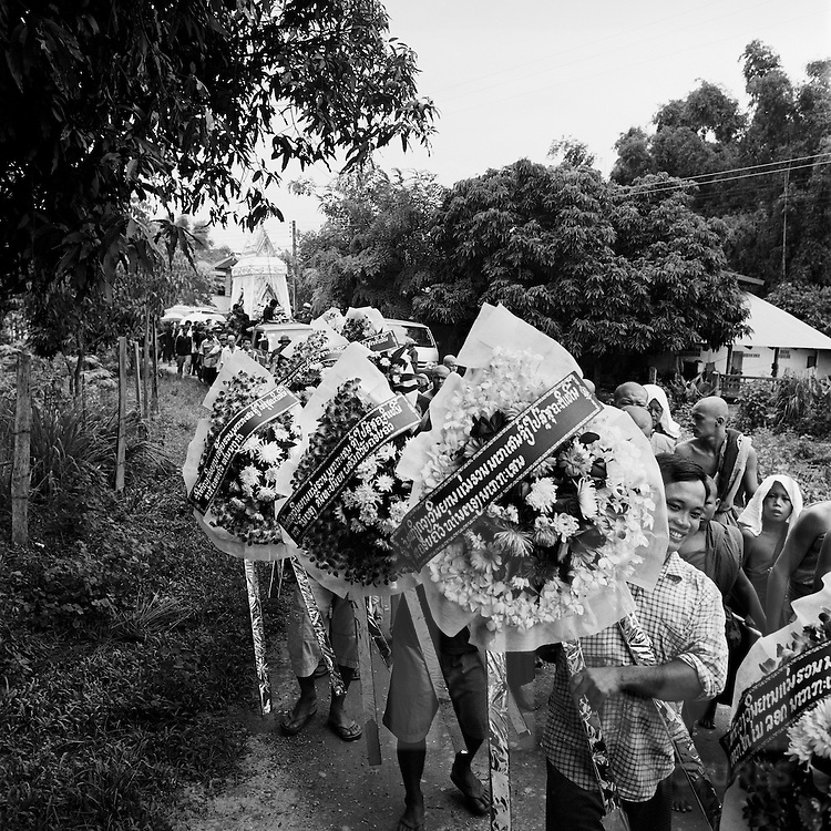 Funeral ceremony, Vientiane Province, Laos, Asia. People carry spray flowers with laos writes honoring the late.