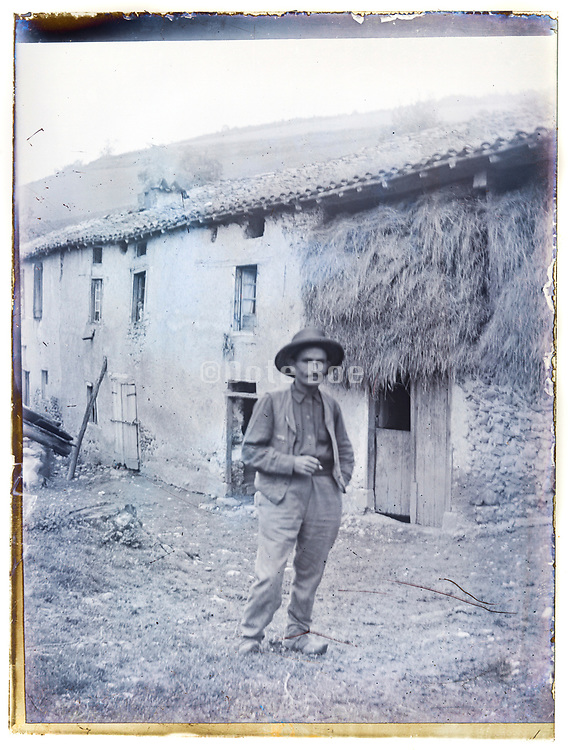 farmer posing in front of farm building deteriorating glass plate France early 1900s