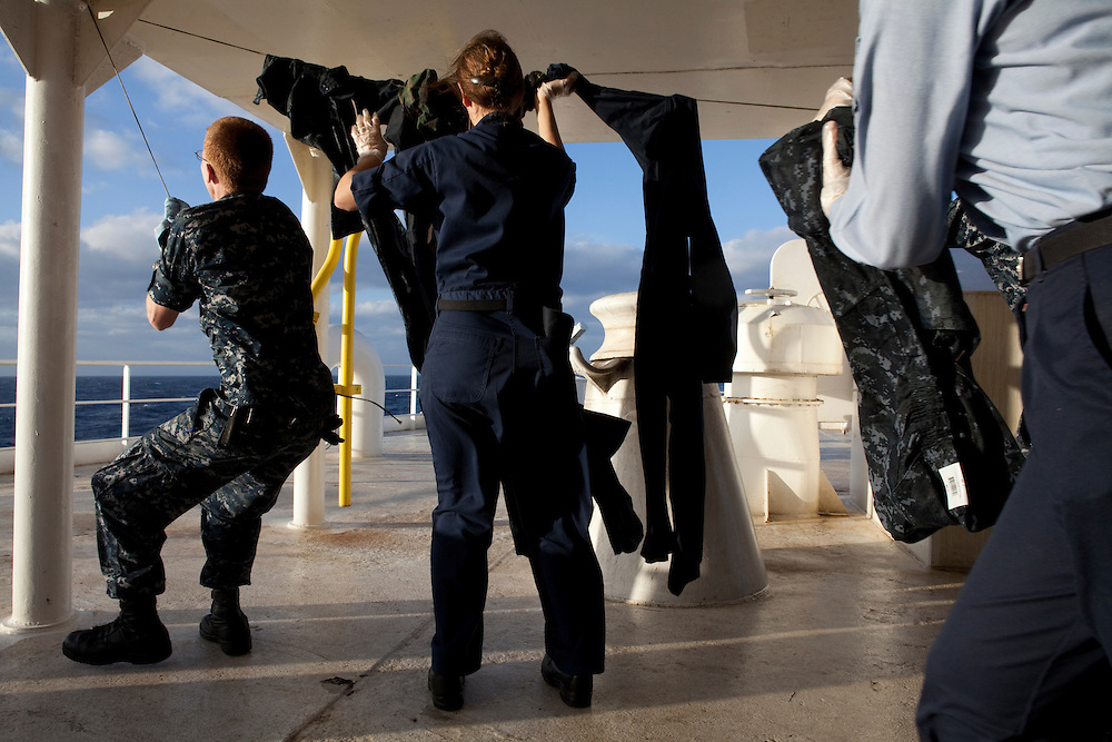 Sailors on board the USNS Comfort, a naval hospital ship, hang their uniforms to dry after soaking them in permethrin to repel mosquitos - and prevent malaria - before landing to help survivors of the earthquake in Haiti on Monday, January 18, 2010 in the Atlantic Ocean off the coast of the United States.