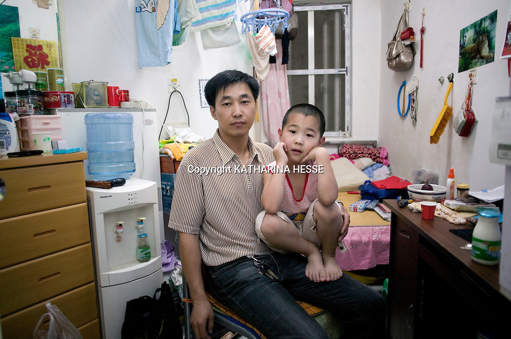 "BEIJING, JULY-21,2010 : Father and son sit in their 5 sm "" apartment"" in the basement of a high rise in Beijing."