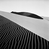 Black and white fine art image of sand dune, the low lying light casts shadows over the ripples at your feet on Dune 17 in Sossusvlei, the Namib desert, Namibia, Africa.