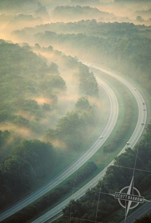 Aerial view of highway cutting through foggy valley.