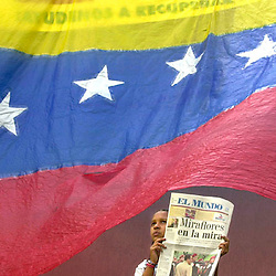 """A young Venezuelan girl sells the daily paper El Mundo that reads """"Miraflores is the Target"""" against the backdrop of the Venezuelan flag. Opponents of President Hugo Chavez were threatening to march on Miraflores, the presidential palace, in the final days of 2002 in an effort to force early elections or Chavez' resignation."""