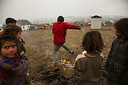 Children play with a small bonfire in a dirty field above the Roma settlement in Huncovce, Slovakia. The kids were unsupervised and playing between open latrines.