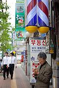 Mann mit Mobil Telefon - Strassenszene im Zentrum der koreanischen Haupstadt Seoul.<br /> <br /> Man with mobile phone - street scene in the center of the Korean Capital Seoul.