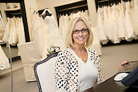 Portrait of a happy senior woman wearing eyeglasses sitting in bridal store