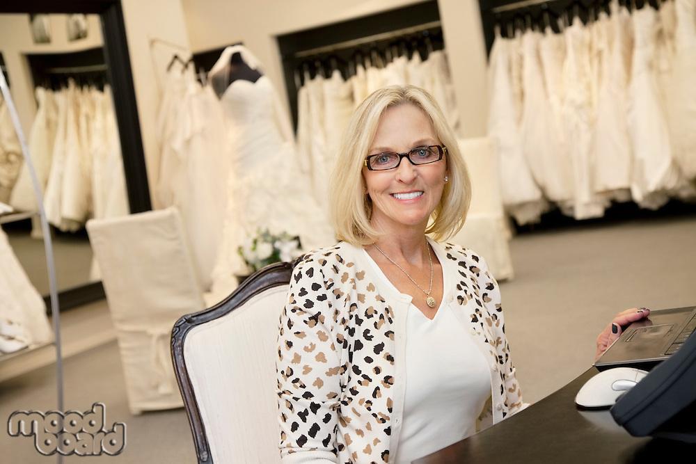 Portrait of a happy senior woman wearing eyeglasses sitting in bridal store