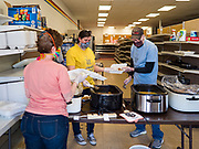 """26 APRIL 2020 - JEWELL, IOWA: MARCIE KNOLL, left back to camera, CARA ZANKER, center and KENN OUTZEN, members of the group trying to reopen a grocery store in Jewell, plate up roast pork dinners for grab and go meals. Jewell, a small community in central Iowa, became a food desert when the only grocery store in town closed in 2019. It served four communities within a 20 mile radius of Jewell. Some of the town's residents are trying to reopen the store, they are selling shares to form a co-op, and they hold regular fund raisers. Sunday, they served 550 """"grab and go"""" pork roast dinners. They charged a free will donation for the dinners. Despite the state wide restriction on large gatherings because of the COVID-19 pandemic, the event drew hundreds of people, who stayed in their cars while volunteers wearing masks collected money and brought food out to them. Organizers say they've raised about $180,000 of their $225,000 goal and they hope to open the new grocery store before summer.           PHOTO BY JACK KURTZ"""