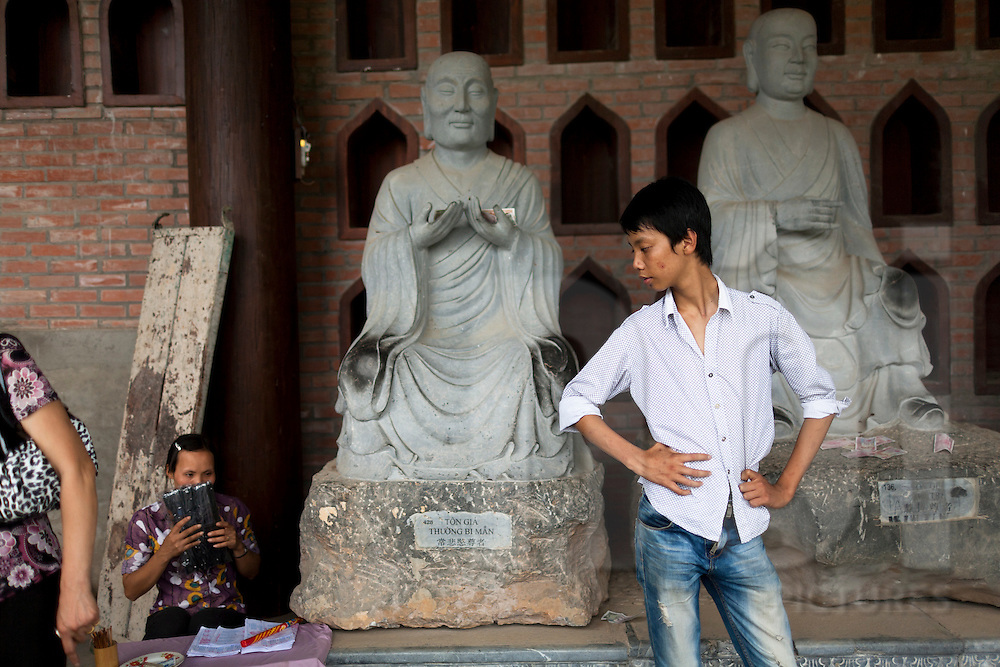 A young vietnamese male stands in front of buddha's statues in Bai Dinh pagoda, considered as the largest complex of Buddhist temples in Vietnam, Asia