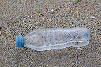 Bottle of water on sandy beach