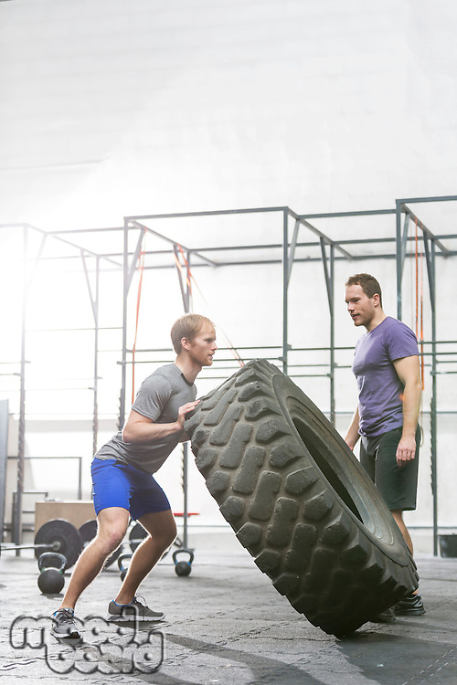 Man looking at dedicated friend flipping tire in crossfit gym