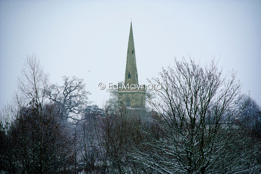 The spire of St Mary and All Saints parish church with ice and snow on the surrounding trees, Stoughton, Leicestershire, England, UK.
