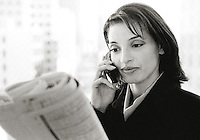 Businesswoman holding mobile phone, reading newspaper (B&W, grainy)