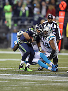 Seattle Seahawks quarterback Russell Wilson (3) gets sacked by Carolina Panthers defensive end Mario Addison (97) and Carolina Panthers defensive tackle Kawann Short (99) forcing a third quarter Seahawks punt during the NFL week 19 NFC Divisional Playoff football game against the Carolina Panthers on Saturday, Jan. 10, 2015 in Seattle. The Seahawks won the game 31-17. ©Paul Anthony Spinelli