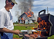 Danville Firefighter Frain (cq) Wagner grills lunch as fellow firefighters burn a house for training Saturday, June 12, 2004, outside Danville, Iowa. Scott Morgan | The Hawk Eye