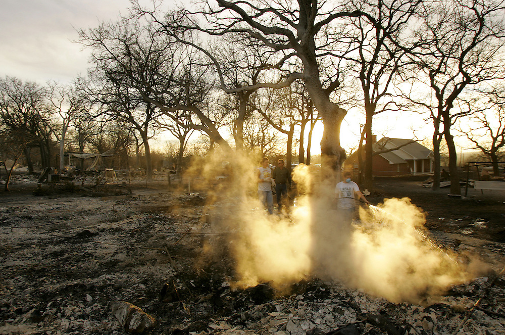 © 2005 Alex Jones www.alexjonesphoto.com..Roni Richards cools off burning debris at the site of her grandmother-in-law's home on Wednesday, December 28, 2005 in Cross Plains, Texas.  The town was heavily damaged by an uncontrolled grass fire on Tuesday, one of many in the state.